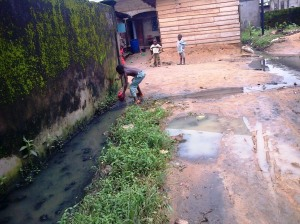 Mambanda, 25 août 2014. Un enfant ramasse une balle dans une eau souillée.