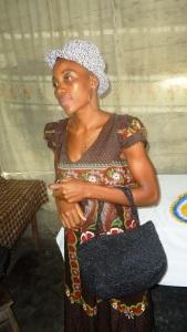 Une dame arbore un chapeau et tient un sac à main faits à base d'emballage plastique recyclé.